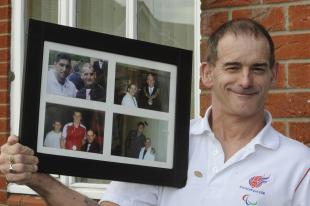 Tony holding a phograph of himself with other athletes.